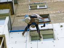 Rope access worker spreading mortar over styrofoam insulation Stock Photo