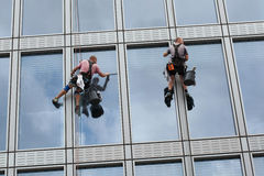 Rope access workers clean windows in office building. PRAGUE, CZECH REPUBLIC - SEPTEMBER 5, 2015: Two rope access workers clean windows in an office building in Stock Photo