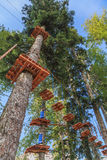 Rope adventure park in a summer forest with blue sky vertical scenic view. Overcoming obstacles and reaching new heights abstract Royalty Free Stock Image