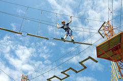 At rope adventure park a young man balancing. On high ropeway with safety equipment Stock Photo