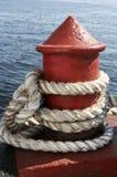Rope Around Red Bitt. White rope rolled up around metal bitt Royalty Free Stock Photography