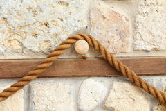 Rope on the background of an old stone wall Stock Images