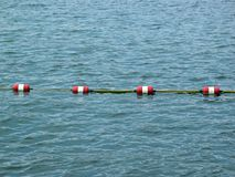 Rope barrier in sea or lake. Rope barrier floating on surface on blue lake or sea stock images