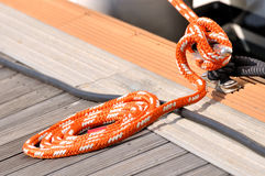 Rope of boat twist into circle on dock. Orange color rope of boat twist on dock board, as a circle, shown as maritime activities, sport or entertainment on sea royalty free stock image