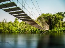 Rope bridge across river. Rope bridge across river over flowing water among the trees Stock Photo