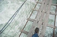 Rope bridge over wild water Royalty Free Stock Photography
