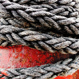 Rope & Capstan. A thick heavy-duty mooring rope tightly secured to a harbour-side capstan - UK Royalty Free Stock Photography