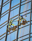 Rope climbers rappelling down Bonaventure Hotel In Los Angeles. Colorful rope climbers rappelling down Bonaventure Hotel In Los Angeles perform for spectators Royalty Free Stock Images