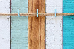 A rope with clips over background of vintage wooden planks in blue, aqua, turquoise and white Stock Images