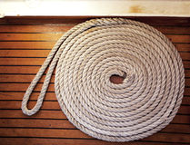 Rope coil across teak decking Royalty Free Stock Photos