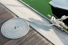 Rope coiled on a wooden dock Stock Images