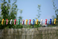 Rope com os grampos plásticos de pano contra o céu azul Imagens de Stock