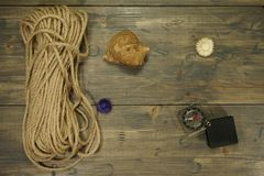 Rope, compass and snail seashell on a wooden table royalty free stock photo