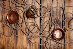 Rope and copper utensils on old wooden burned table or board for Royalty Free Stock Photo