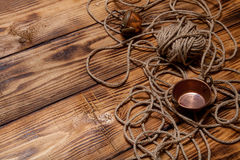 Rope and copper utensils on old wooden burned table or board for Royalty Free Stock Photography