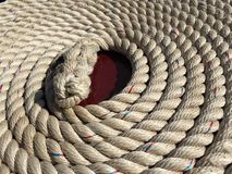 Rope curl. The bow rope from an English narrowboat barge sits in the late afternoon sun showing off a great texture Stock Images