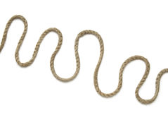 Rope curls. A length of old thin rope arranged in curls, on white background, shot from above royalty free stock photos