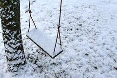 Rope das Schwingen, das von einem Baum hängt, der mit Schnee bedeckt wird Lizenzfreie Stockbilder