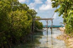Rope die Hängematten, die über Lagunenwasser auf Tropeninselferienparadies für die Entspannung verschoben werden Lizenzfreies Stockfoto