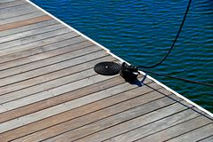 Rope on dock. Coiled rope from docked boat on wooden pier Royalty Free Stock Image