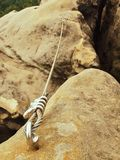 Rope end anchored for climbers into sandstone rock. Iron twisted rope fixed with srew clamps in block. Safety footpath between roc Stock Images