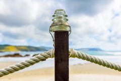 Rope fence on wooden pillar with glass lamp on beach. Stock Photo