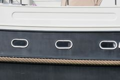 Rope fender on the side of a boat. Rope fender protects a boat below the portholes Stock Photos