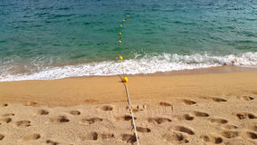 Rope with floats and footprints on sandy beach Royalty Free Stock Photo