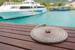 Rope folded in circle shape by the pier and speed boat Stock Images