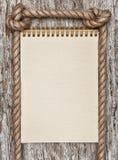 Rope, gewundenes Papiernotizbuch und Holzhintergrund Stockfoto
