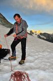Rope on glacier. French Guide measuring out rope prior to a glacier traverse at dawn Stock Images