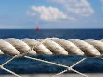 Rope guard with red sail on the background Royalty Free Stock Photos