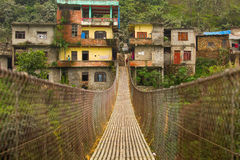 Rope hanging suspension bridge in Nepal with colorful village in Royalty Free Stock Image