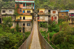 Rope hanging suspension bridge in Nepal with colorful village in Royalty Free Stock Photos