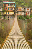 Rope hanging suspension bridge in Nepal with colorful village in Stock Photography