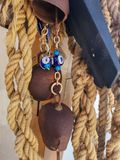 The rope hanging up, the eye beads and the cow bell. stock photography