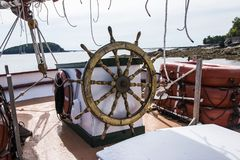 The helm of a wooden sailboat with porcupine island in the background royalty free stock photo