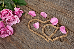 Rope hearts with rose petals Stock Image