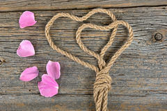 Rope hearts and rose petals Royalty Free Stock Photos