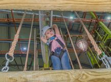 The rope at the height of holds in the adventure Park the kid in. Girl in a white helmet at the adventure Park at the height of holding the rope Stock Images