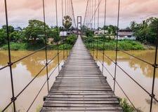 Rope il ponte sospeso attraverso un fiume in inondazione, Tailandia Immagine Stock Libera da Diritti