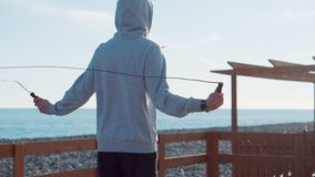 Rope jump exercise. Back view of man in hoodie skipping on waterfront. Everyday outdoor workout stock video