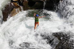 Rope jumping. Caucasian man rope jumping in rapid waters of a river Stock Images