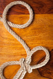 Rope with a knot. Rope knot on a teak wood background Royalty Free Stock Photo