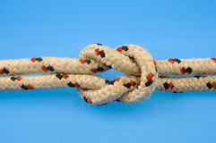 Rope Knot. A knot in a rope used for rock climbing, on a blue background Royalty Free Stock Images