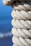 Rope knot on a jetty at the sea Royalty Free Stock Photo