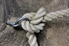 Rope Knot. Thick rope knot tied to the ring on the wall Royalty Free Stock Photos