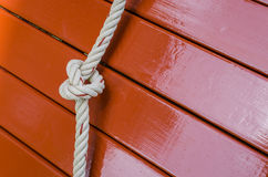Rope knot and wood panel Royalty Free Stock Image