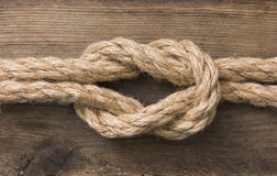 Rope with knots. On the background of the old wooden boards royalty free stock images