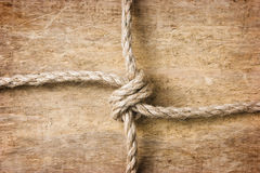 Rope with knots. On the background of the old wooden boards stock image